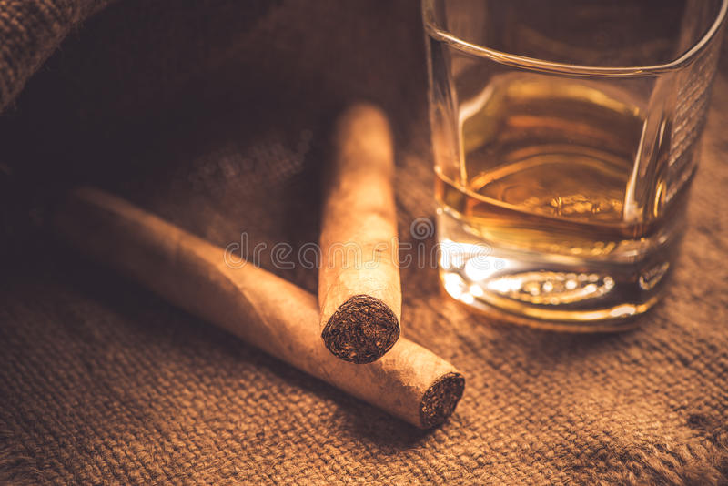 Whisky and cigars. Glass of whisky and two cigars on jute