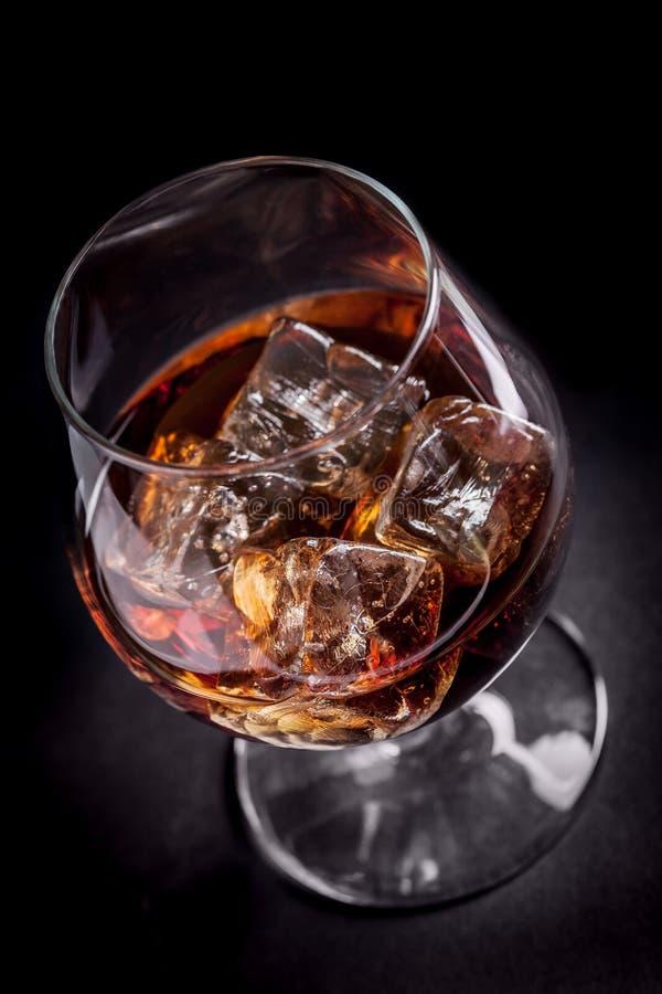 Whisky/cognac su priorità bassa nera fotografia stock
