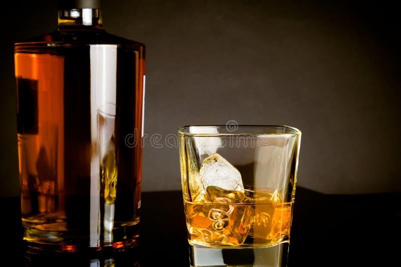Whisky con hielo en la botella cercana de cristal en fondo oscuro fotos de archivo libres de regalías