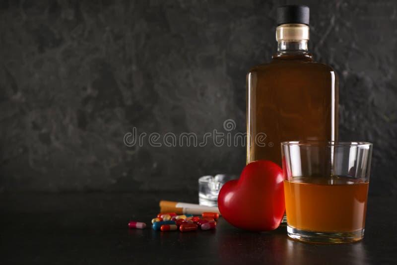 Whisky con las drogas, los cigarrillos y el corazón en la tabla oscura Concepto de alcoholismo fotografía de archivo