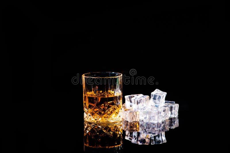 Whisky con los cubos de hielo en fondo negro fotos de archivo