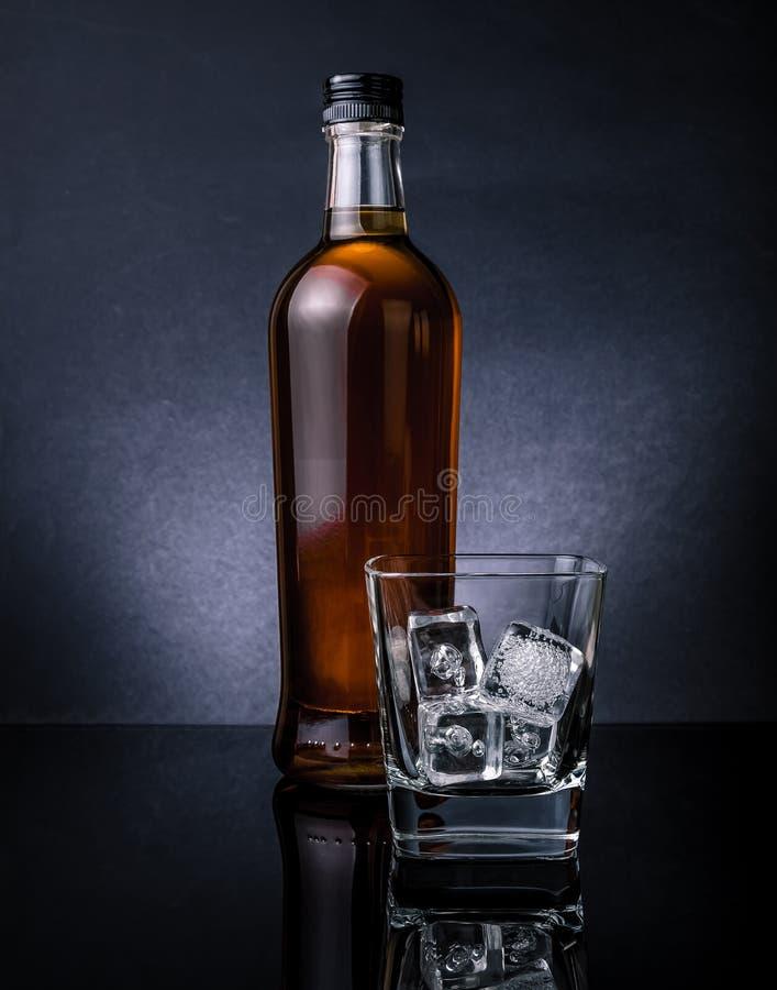 Whisky con los cubos de hielo en la botella cercana de cristal en el fondo negro, atmósfera fría fotografía de archivo