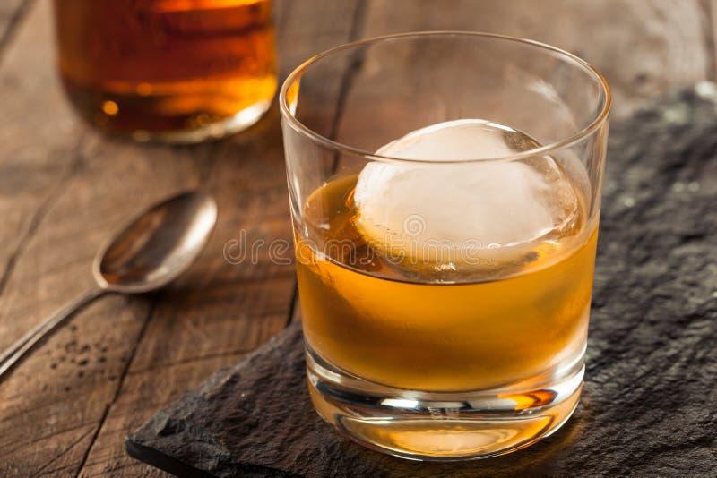 Whisky de Borbón con un cubo de hielo de la esfera foto de archivo