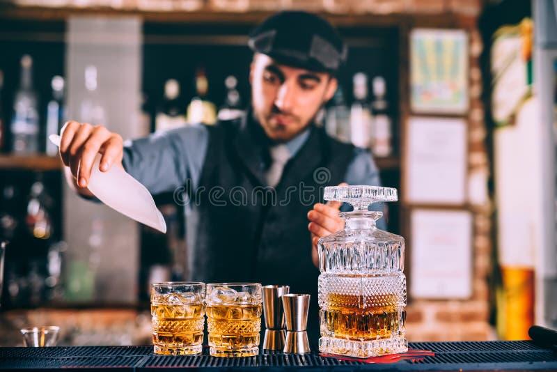 whisky de colada e hielo del camarero elegante en los cócteles frescos en barra moderna imágenes de archivo libres de regalías