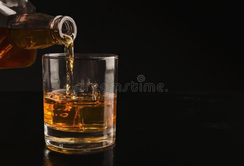 Whisky de colada de la botella en el vidrio con hielo imagen de archivo libre de regalías