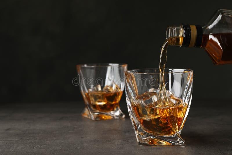 Whisky de colada de la botella en el vidrio con los cubos de hielo en la tabla fotos de archivo