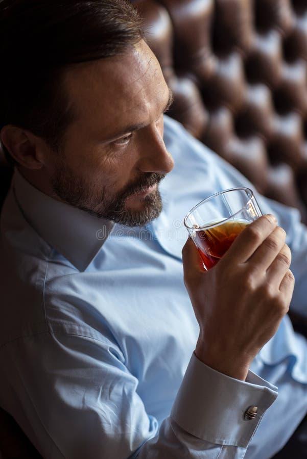 Whisky de consumición del hombre brutal confiado foto de archivo libre de regalías