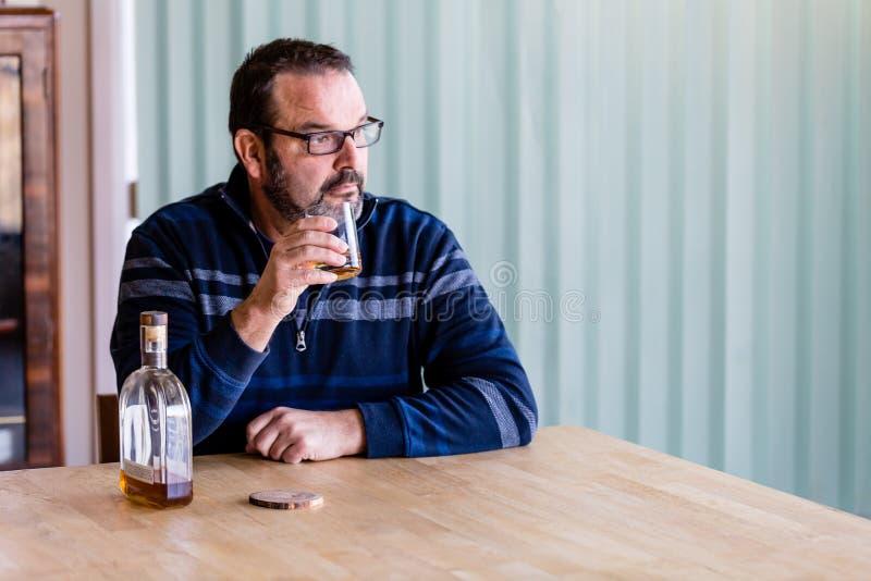 Whisky de consumición del hombre mayor con una botella casi vacía al lado de él fotos de archivo libres de regalías