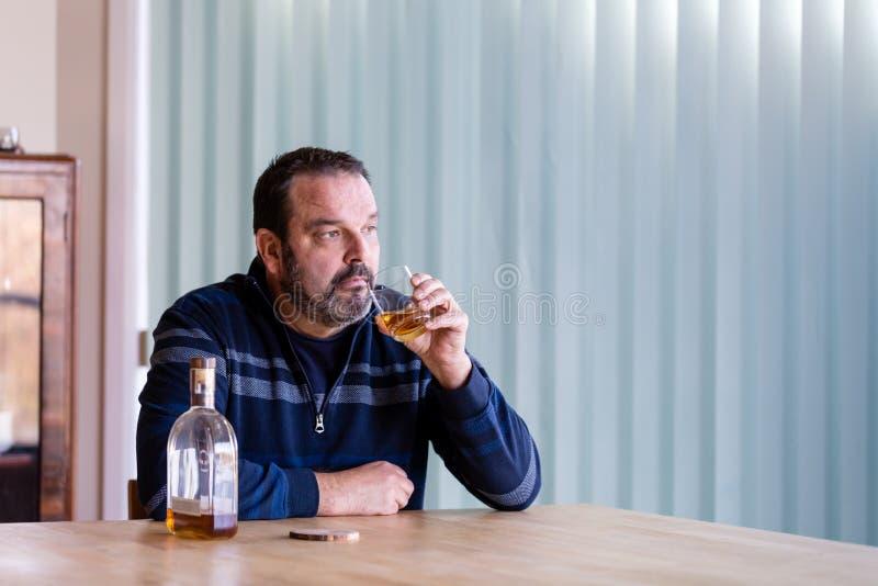 Whisky de consumición del hombre mayor con una botella casi vacía al lado de él imágenes de archivo libres de regalías
