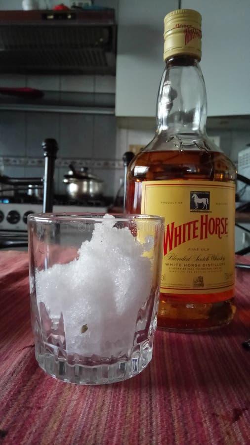 Whisky del caballo blanco con un vidrio de nieve foto de archivo libre de regalías