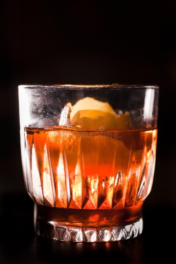 Whisky en Campari-cocktail met sinaasappelschil wordt versierd die stock foto