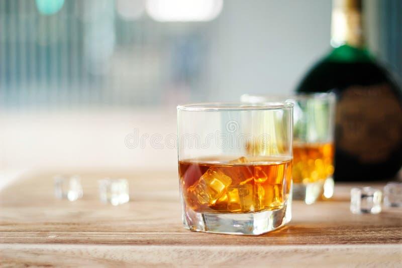 Whisky en dos vidrios y botellas en un fondo de madera de la tabla imágenes de archivo libres de regalías