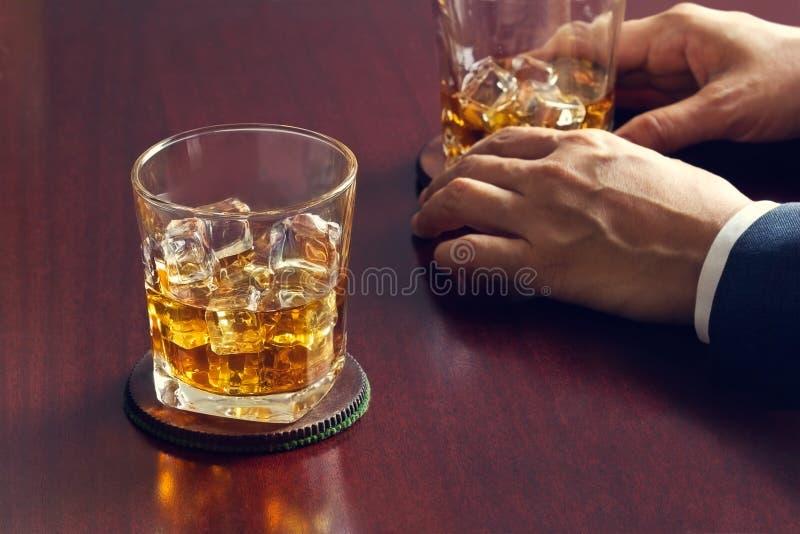 Whisky en la tabla de madera y hombre de negocios con el whisky a disposición fotos de archivo