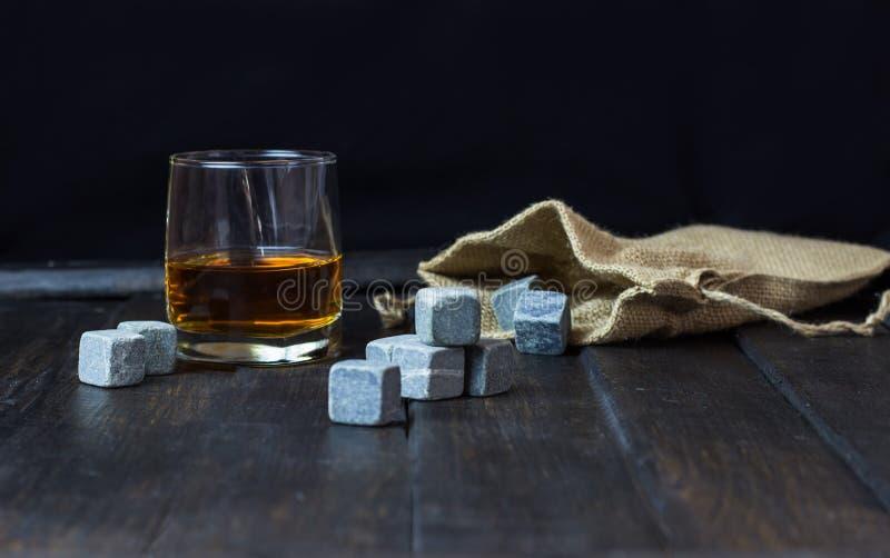 Whisky en un vidrio con las piedras para las bebidas de enfriamiento en una tabla de madera fotos de archivo