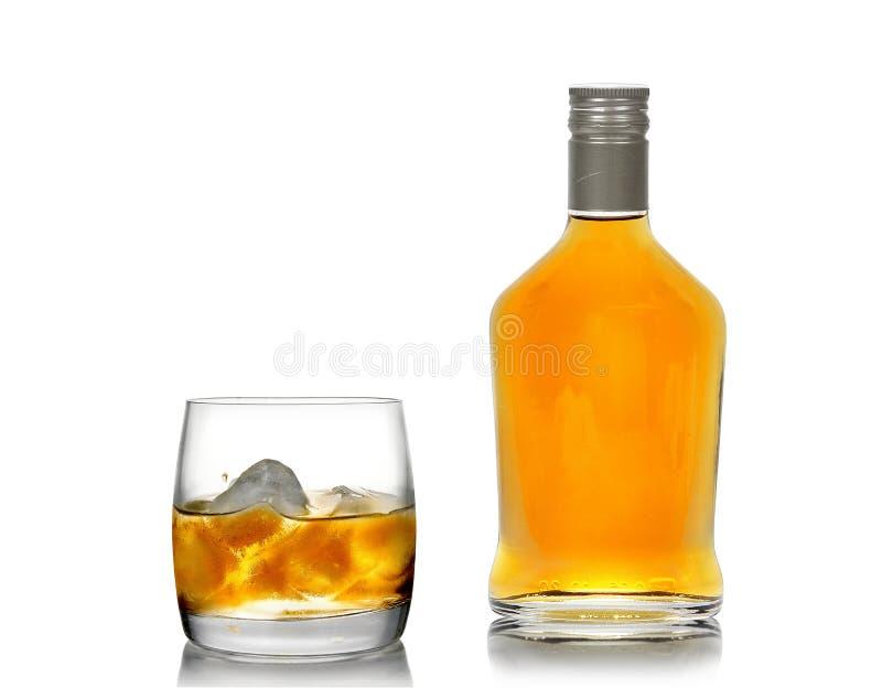 Whisky en un vidrio (con un hielo) y una botella imágenes de archivo libres de regalías