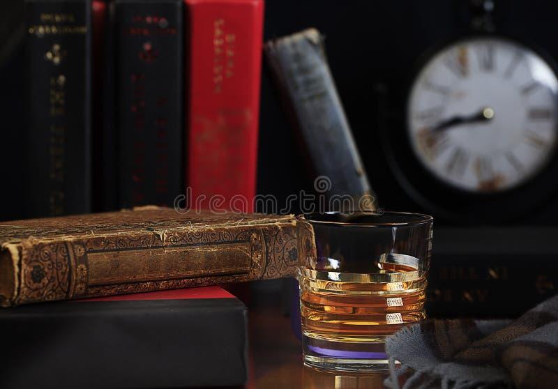 Whisky escocés aseado con los libros y el reloj fotos de archivo