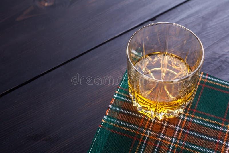 Whisky escocés en el tartán foto de archivo