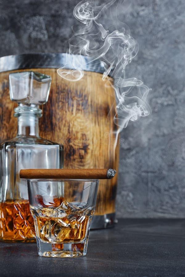 Whisky escocés fuerte de la bebida alcohólica con los cubos de hielo en vidrio viejo de la moda y la jarra cristalina con el ciga fotografía de archivo libre de regalías