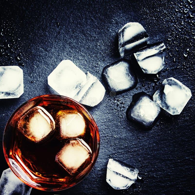 Whisky frío con el hielo, fondo negro, visión oscura, superior imagenes de archivo