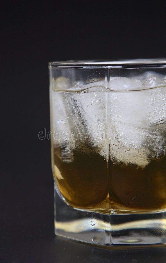 Whisky in a glass with ice. Against a dark background stock image