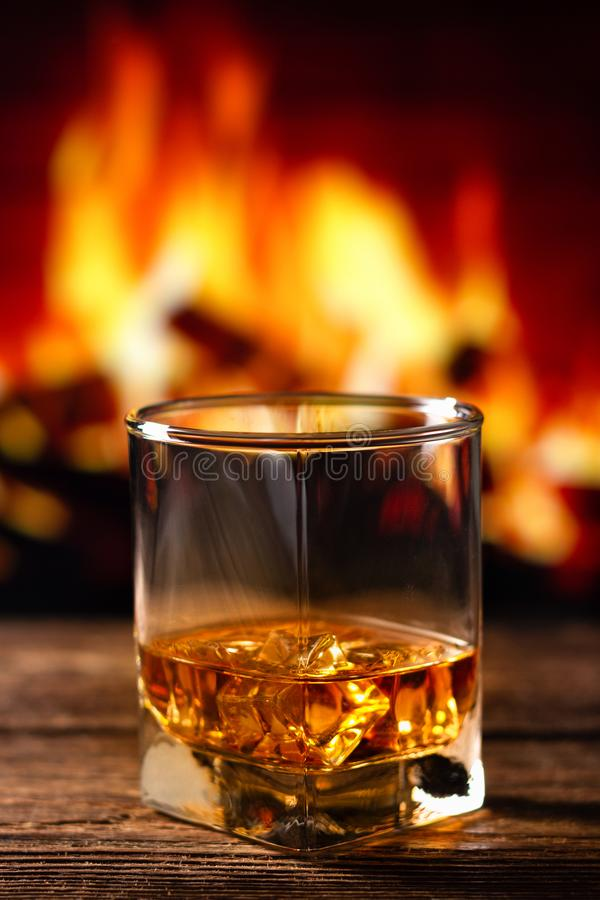 Whisky i ett exponeringsglas med brand i spisen på bakgrunden royaltyfria bilder