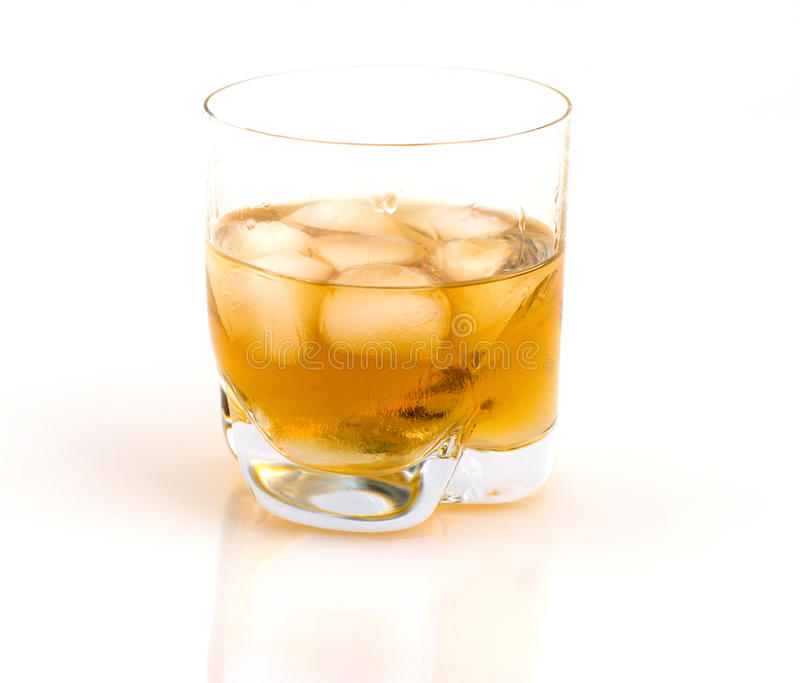 Whisky with ice. Glass of whisky with ice on a white background royalty free stock image