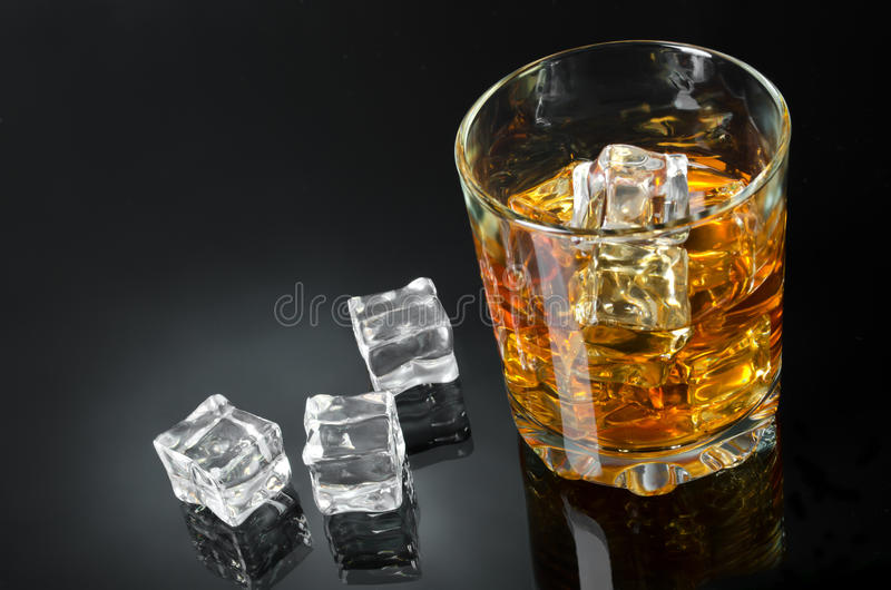 Whisky with ice. Glass of whisky with ice on a black backdrop stock image