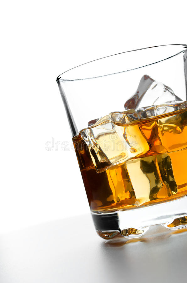 Whisky with ice. Glass of whisky with ice on a white backdrop stock photos