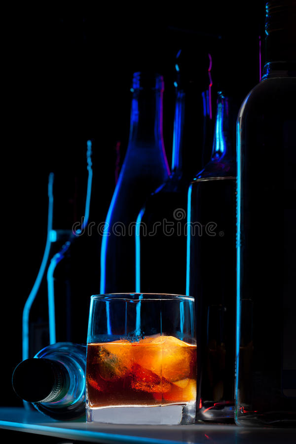 Whisky with ice. And silhouettes of bottles on dark bar background stock photography