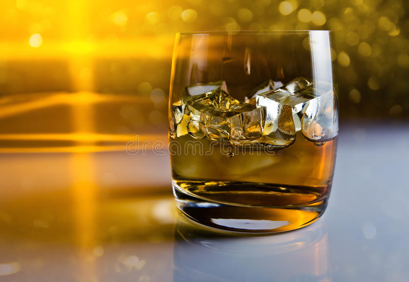 Whisky with ice. On a reflective background royalty free stock image