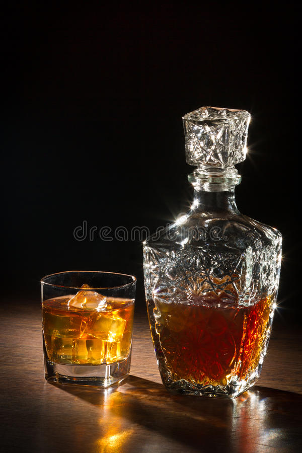 Whisky on ice and glass carafer. On black background stock image