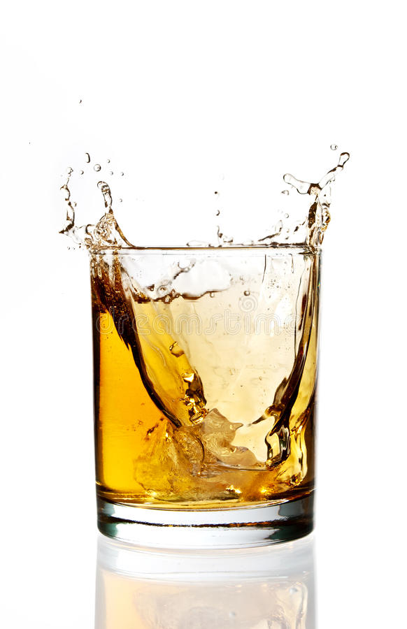 Whisky ice splash. Ice falling and splashing into a glass of whisky royalty free stock photo