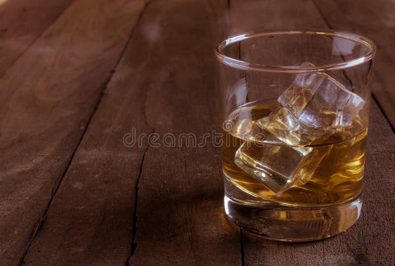 Whisky im Glas mit Eiswürfeln auf Holztisch lizenzfreies stockfoto