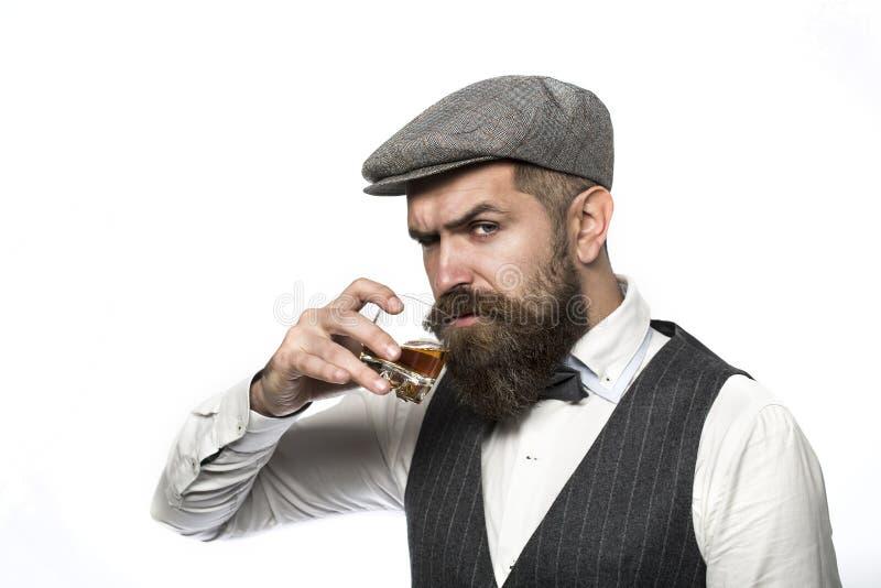 Whisky konjak, konjakdrink Brutal skäggig man med exponeringsglas av whisky, konjak, konjak Attraktiv man med en konjak royaltyfri bild