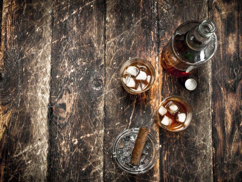 Whisky med is och en cigarr arkivfoton