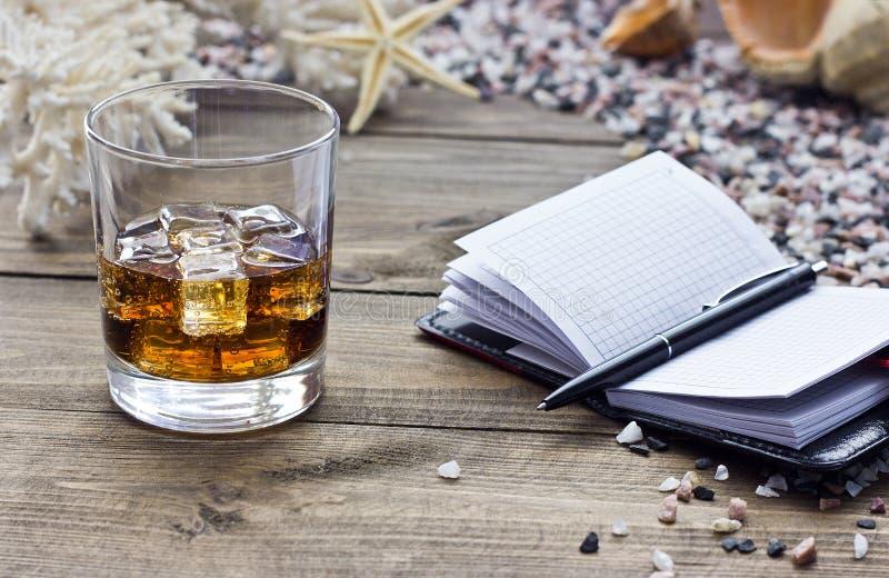 Whisky met een notitieboekje stock afbeeldingen