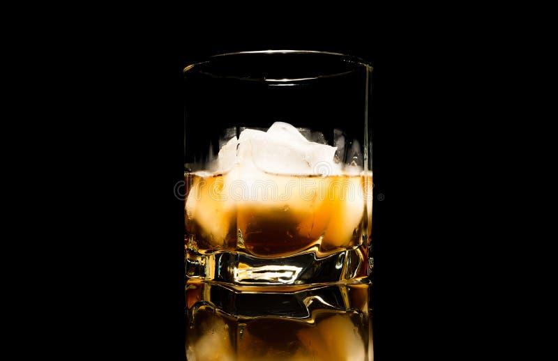 Whisky mit Eisabschluß oben auf einem Glastisch lokalisiert auf einem schwarzen Hintergrund lizenzfreies stockbild
