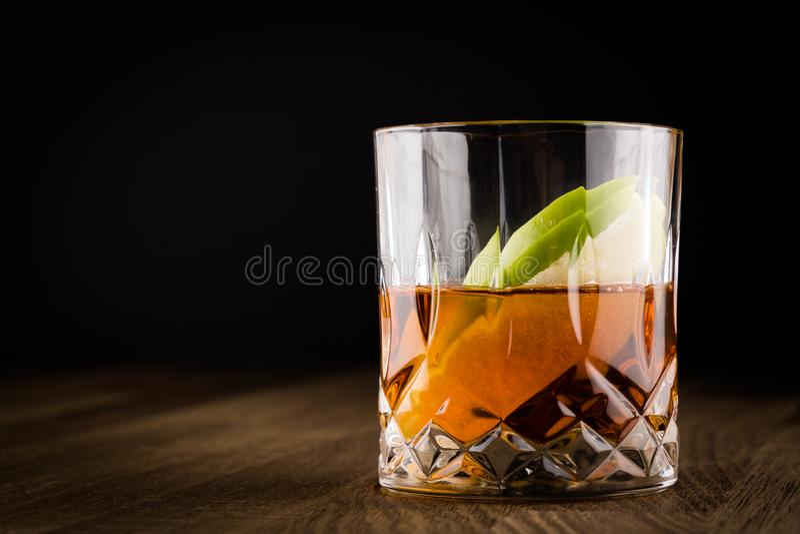 Whisky mit Scheiben von grünem Apple auf Holztisch und schwarzem Hintergrund lizenzfreies stockfoto