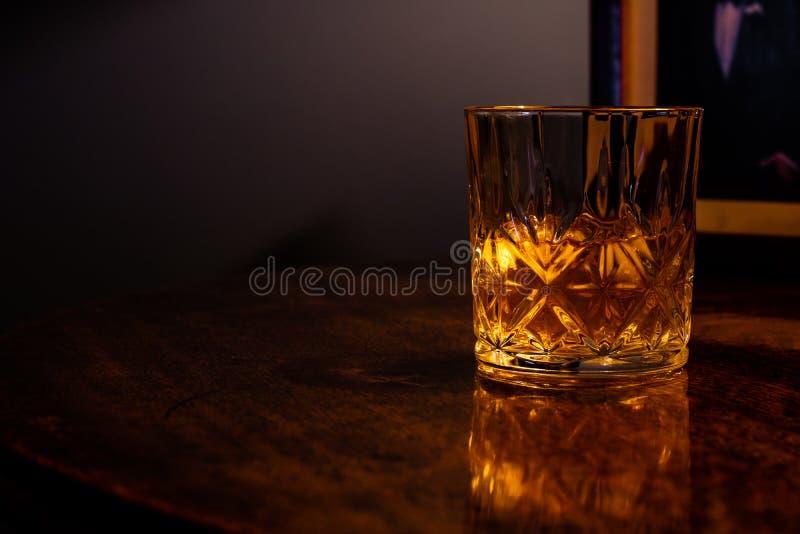 Whisky op de rotsen in een kristaltuimelschakelaar stock afbeeldingen