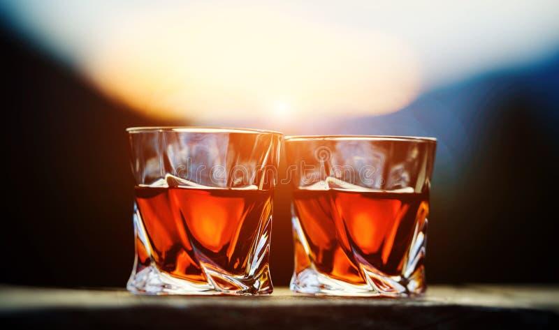 whisky przy zmierzchu dramatycznym niebem na g?ra krajobrazu tle obraz stock