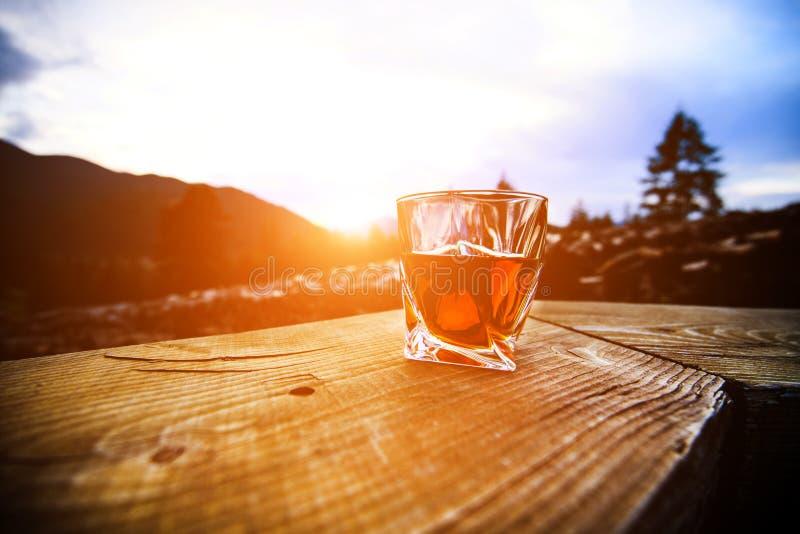 whisky przy zmierzchu dramatycznym niebem na g?ra krajobrazu tle zdjęcie royalty free
