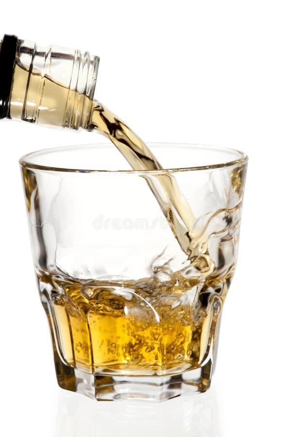 Whisky que vierte en el vidrio, aislado, camino de recortes fotos de archivo libres de regalías