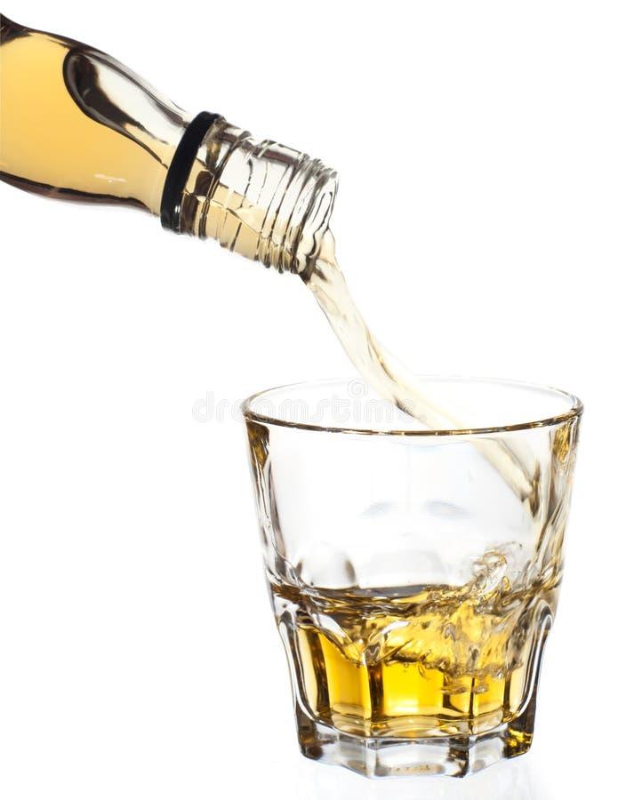 Whisky que vierte en el vidrio, camino de recortes foto de archivo