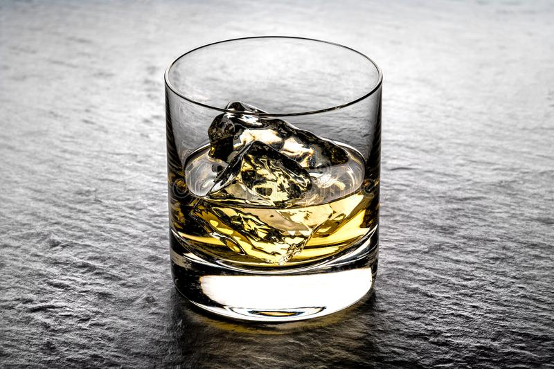 Whisky on the rocks in a glass tumbler. Shining on a black slate background royalty free stock photos