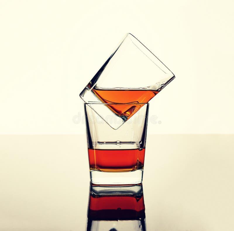 Whisky, rum lub koniak w dwa szkłach na stole z odbiciem, Pojęcie: luksusowy alkohol obrazy stock