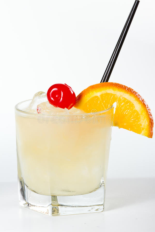 Whisky sour. Traditional whiskey sour cocktail served on the rocks garnished wiht a red cherry and an orange slice royalty free stock images