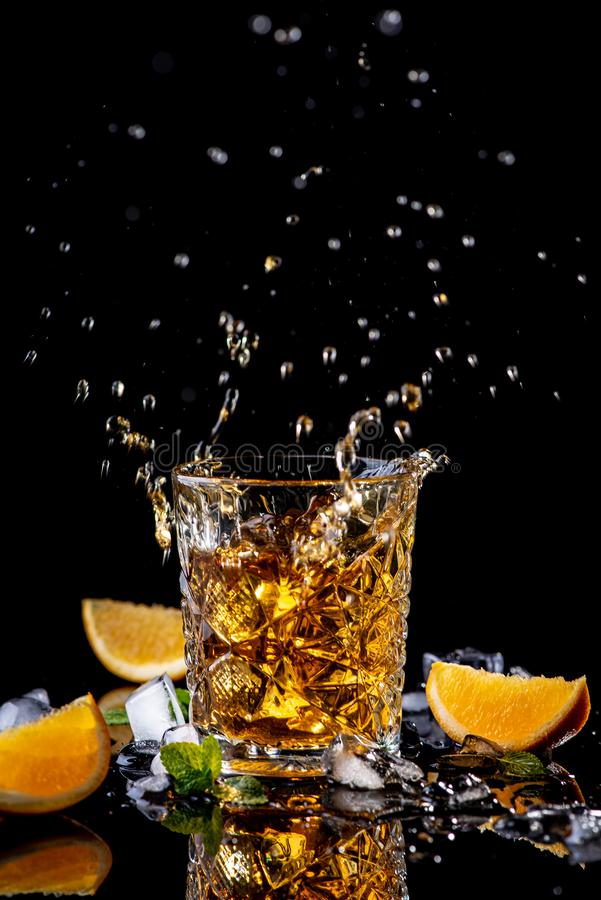 Whisky splash. Glass of Whiskey decorated with orange, green mint and pieces of ice. On a black background with reflection, studio royalty free stock images