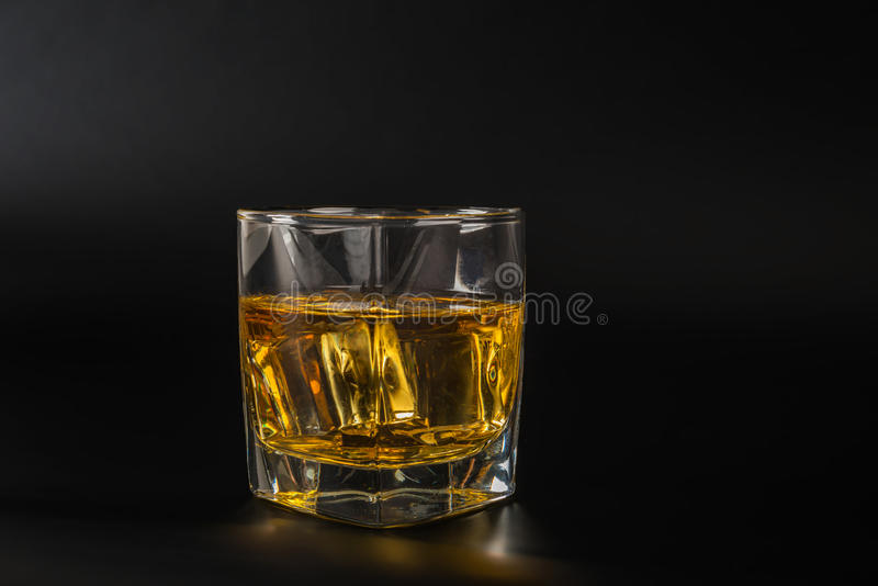 Whisky tasting glass, whiskey in a glass, black background, ice. Cubes, party night royalty free stock photos