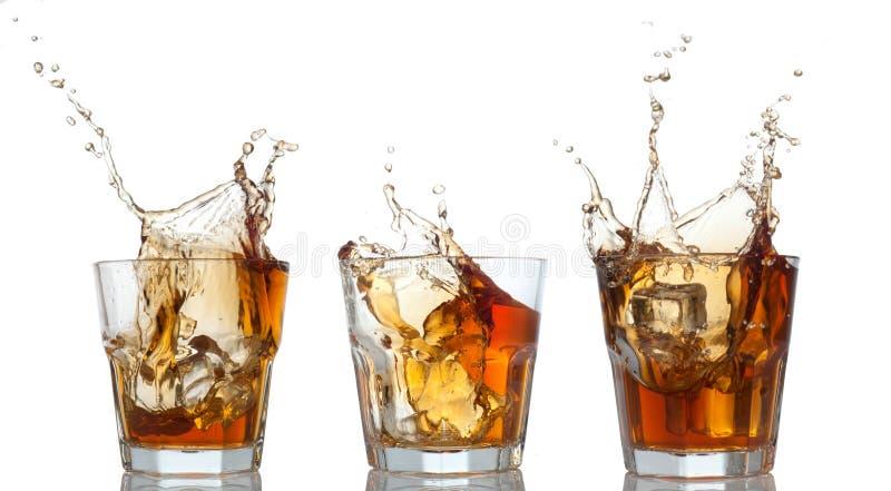 Whisky ustalony chełbotanie z szkła na bielu obraz royalty free