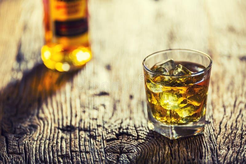 whisky Whiskygetränk mit Eiswürfeln auf altem rustikalem eichenem Tisch stockfotos